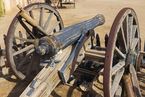 Vintage Old Wild West Wooden Canon in Mexican Hacienda Courtyard supported by rusted Wheels