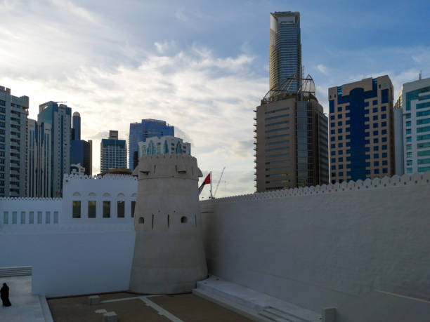 old (vintage) middle eastern building  and towers surrounded by modern skyscrapers - qasr al hosn in abu dhabi city - uae national day стоковые фото и изображения
