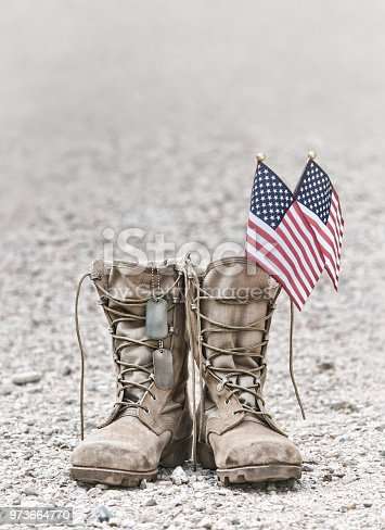 Old military combat boots with dog tags and two small American flags. Rocky gravel background with copy space. Memorial Day or Veterans day concept. Vintage tone.