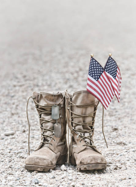 Old military combat boots with dog tags and the American flags stock photo