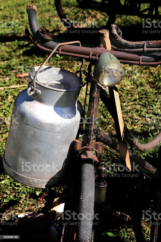 old Milk Canister and rusty historic bike milkman stock photo