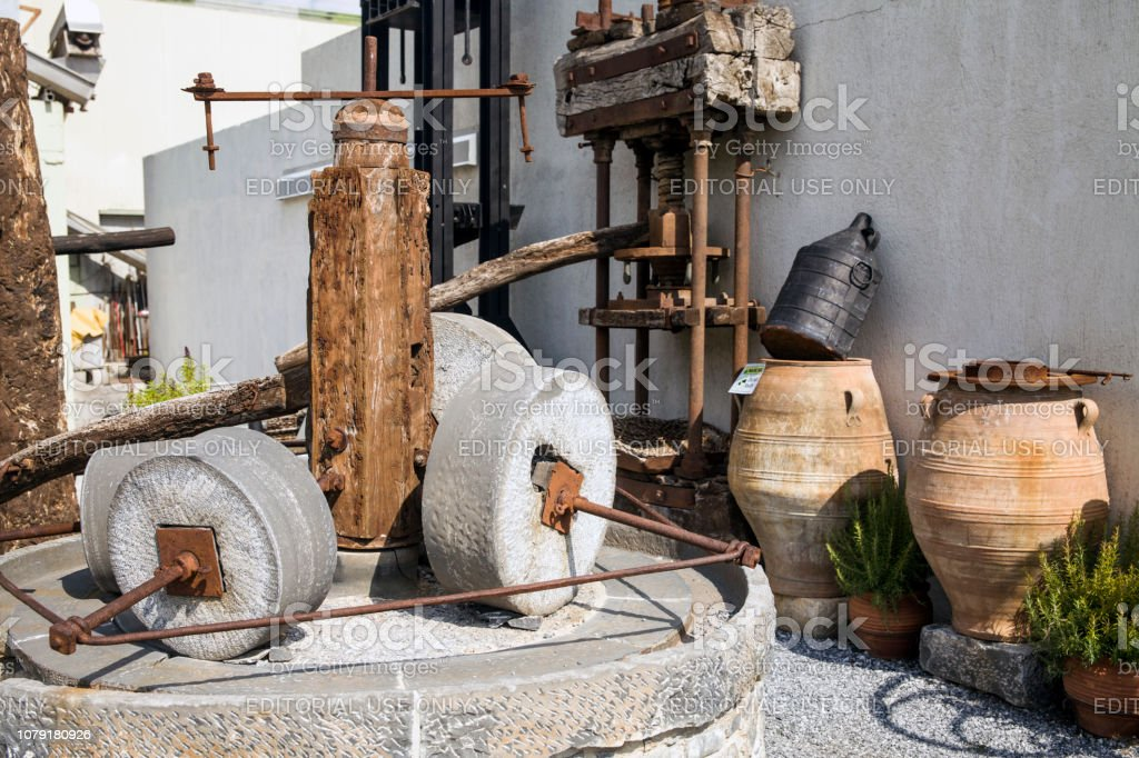 Old mill for grinding olives. An antique machine for producing olive oil. stock photo