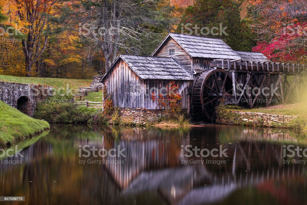 Old mill reflecting in mill pond in autumn stock photo