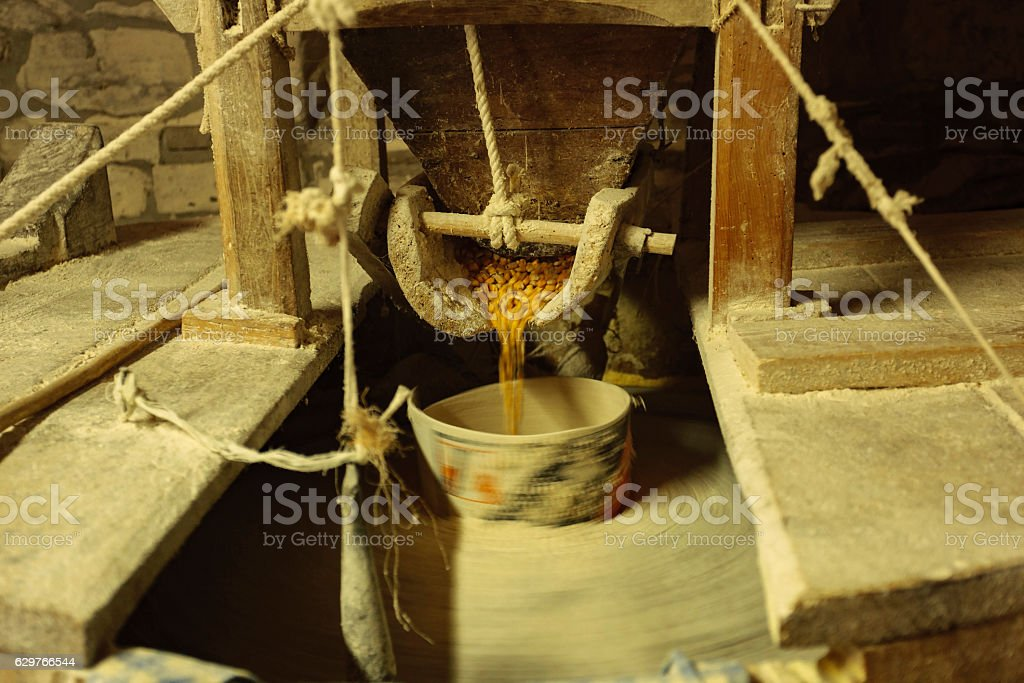 Old mill with millstone for grain stock photo