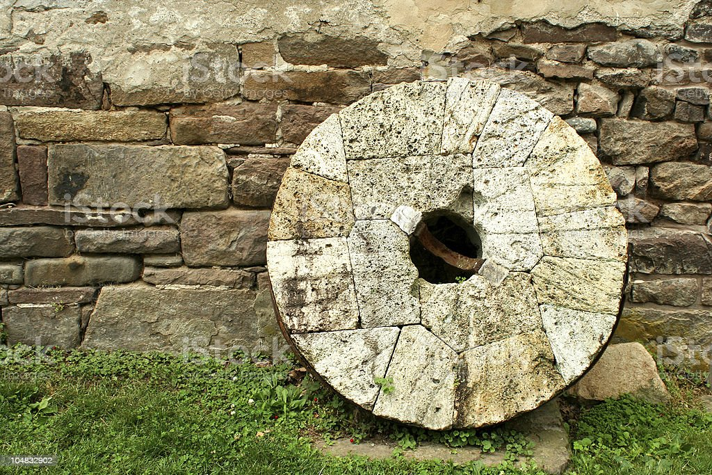 Old millstone leaning on a wall stock photo