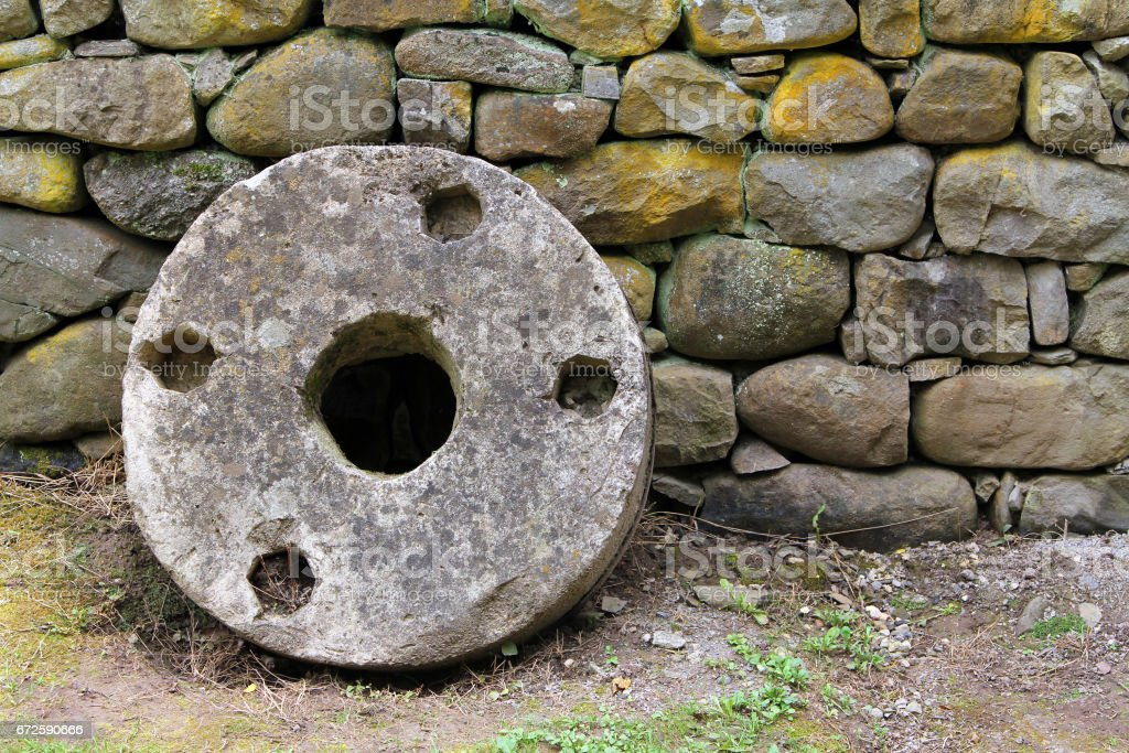 Old millstone on a background of stone wall, Etar, Bulgaria stock photo