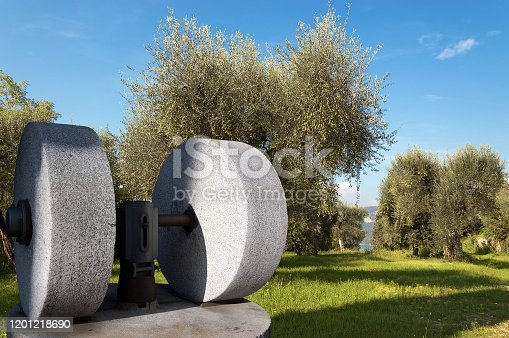 Two old millstones for the production of olive oil with a green olive grove on the background