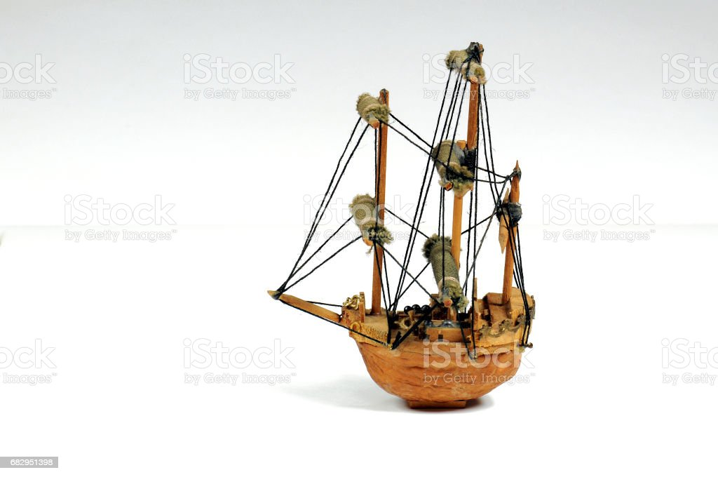 Old miniature sailboat made with a nut shell. Isolated on white. royalty-free stock photo