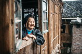 old minority chinese woman looking out of window of wooden house