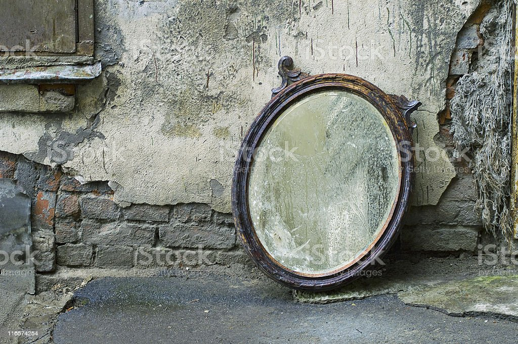 Old mirror leaning against an old wall exposing bricks stock photo