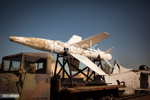 Old missile sitting on a truck in a salvage yard