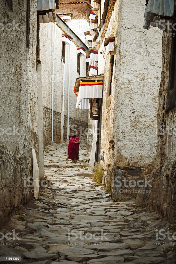Old monk walking in the narrow street stock photo