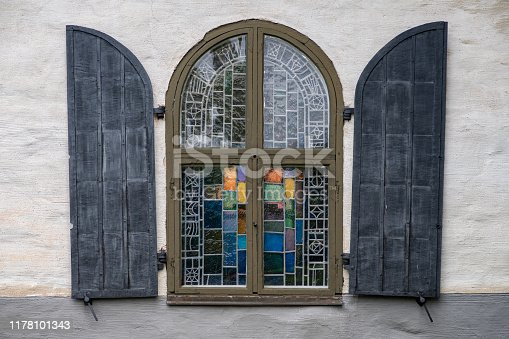 Vaulted and colorful mosaic window from an old church in Sweden with lead ornaments and colorful glass and protective cover doors on the side