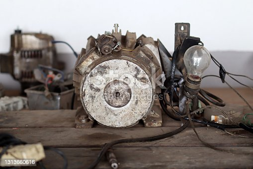 Old motor put on workshop table in car service shop, repairing process in the garage