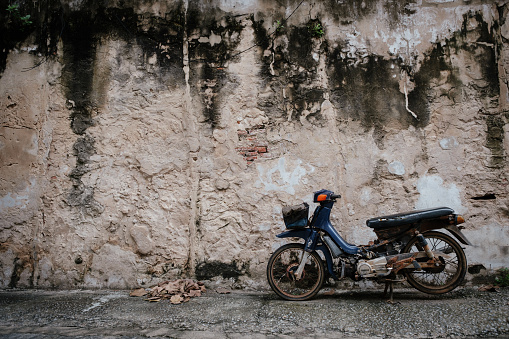 Old motorcyle with Old wall texture background  in Bangkok, Thailand