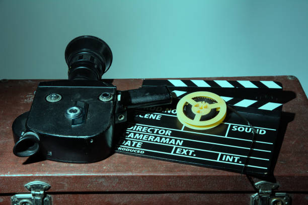 Old movie camera clapper and reel with a film stock photo