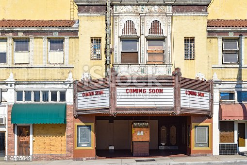 The facade of an old movie theater with Coming Soon on the marquee.