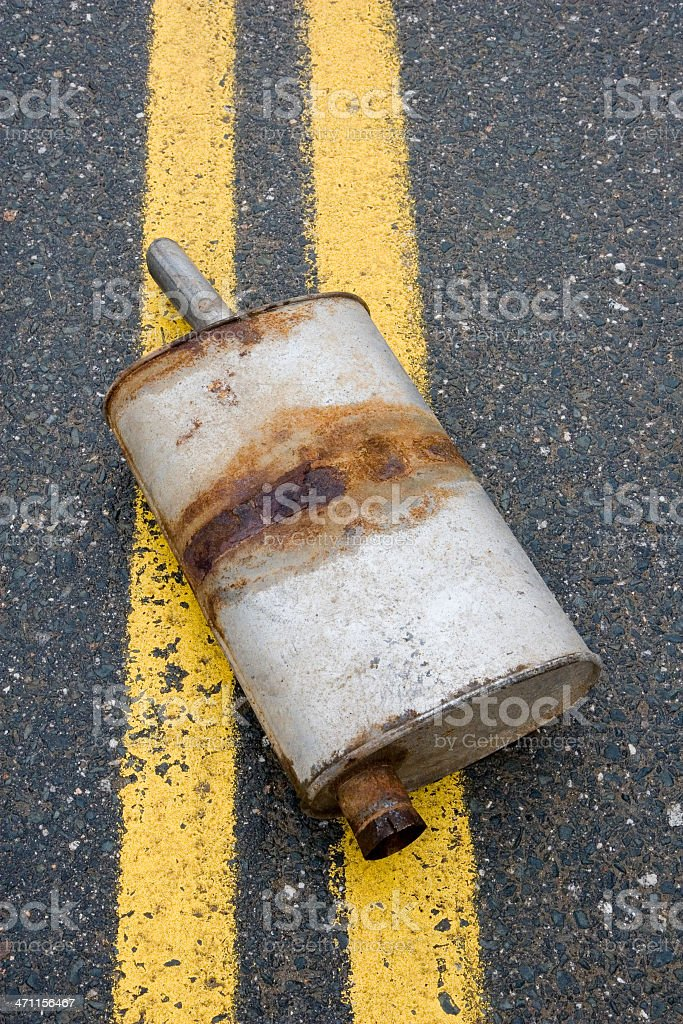 Old muffler in the road stock photo