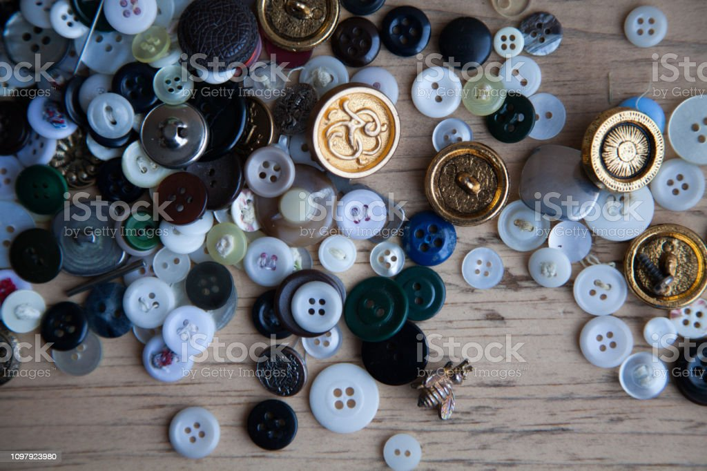 Old multi colored button collage on wood backdrop