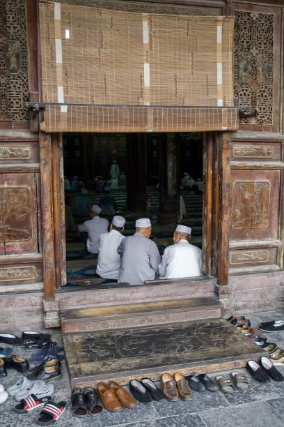 gamla muslimska kinesiska män be vid xian stora moskén i staden av xian. - hui architecture bildbanksfoton och bilder