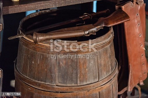 istock Old muzzleloader pistol standing on an antique wooden barrel 1139727284
