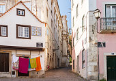 Old narrow street in Lisbon Portugal with hanging clothes