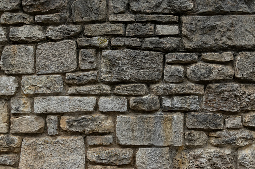 Old natural stone wall of gray and yellowish stones in different sizes