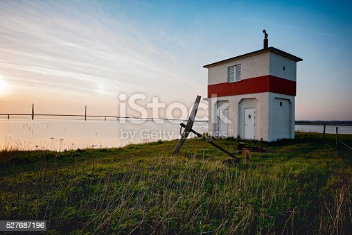 Early evening picture of the old navigation hut and lighthouse that overlooks the Grønsund between the islands of Falster to the left and the main island of Zealand. In the background can be see the modern bridge that links the two islands. A long exposure has been used to blur the sea and the grasses in the foreground.
