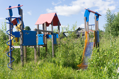 Old neglected playground equipment, overgrown with weeds.