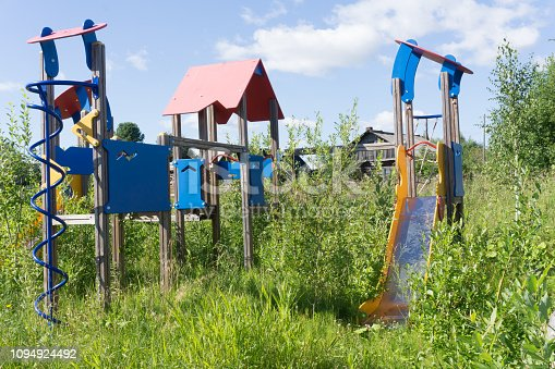 Old neglected playground equipment, overgrown with weeds