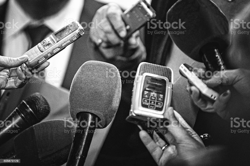 Old news Journalists with recording equipment flocking around important people. Black and white retro style processing 70-79 Years Stock Photo