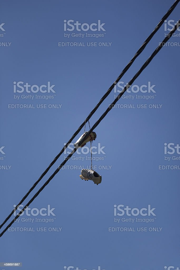 Old Nike Soccer Shoes hanging on Power Cable stock photo