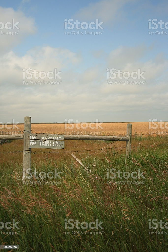 old 'no hunting' sign on a Southern Alberta field royalty-free stock photo