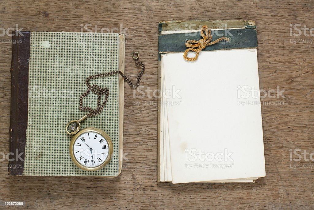 Old notepad, antique book, pocket watch on wood royalty-free stock photo