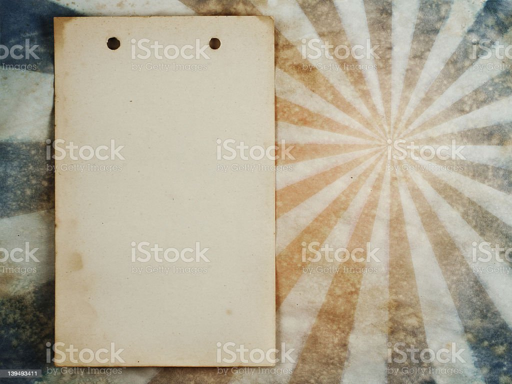 Old notepad sheet on sunburst background stock photo