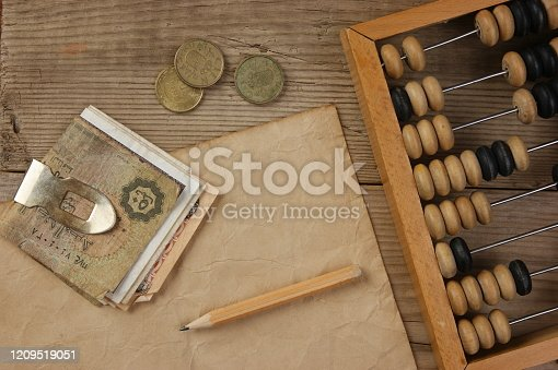 istock Old notes and coins and abacus on a wooden table 1209519051