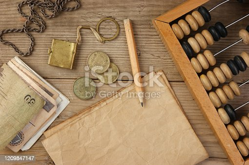 istock Old notes and coins and abacus on a wooden table 1209847147
