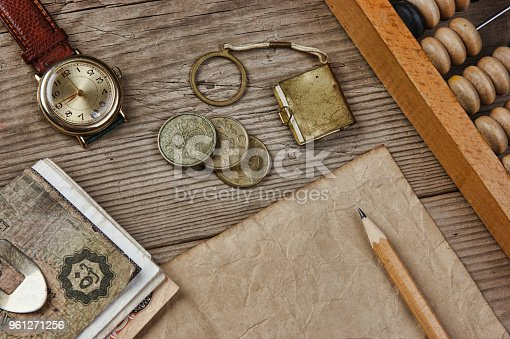 istock Old notes and coins and abacus on a wooden table 961271256