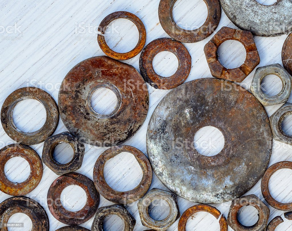 old nuts and washers on wooden white background stock photo