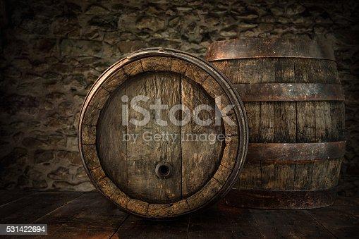 istock Old oak barrels on blurred cellar wall 531422694