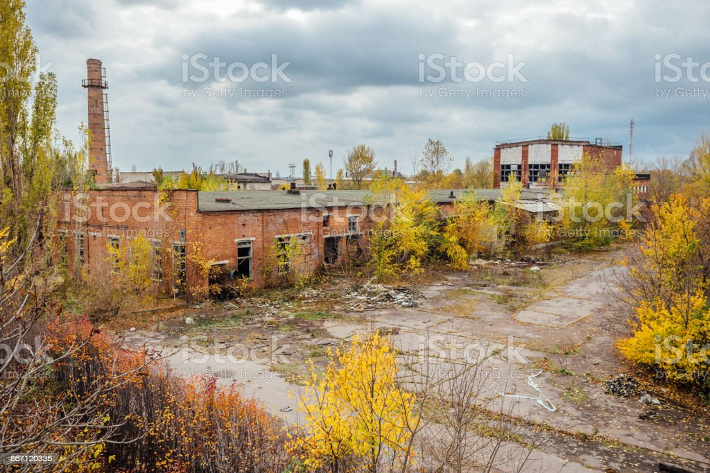 Old obsolete ruined overgrown concrete industrial buildings in autumn. Abandoned factory stock photo