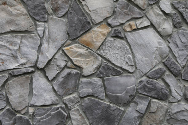 old odd shaped grey black thick cut stone block wall with gray grout shadows straight lines suitable for website background marketing backgrounds backdrops architecture architectural layout design stock photo