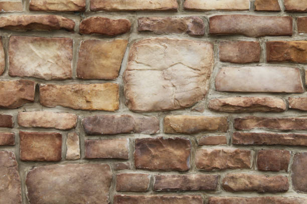 old odd shaped tan and brown thick cut stone block wall with grout shadows and straight lines suitable for website background marketing backgrounds backdrops architecture architectural layout design stock photo