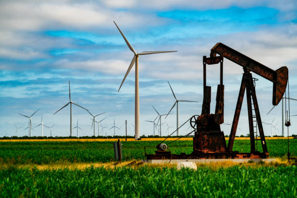 Old Oil Pump in front of Huge Wind Turbines in Wind Farm stock photo