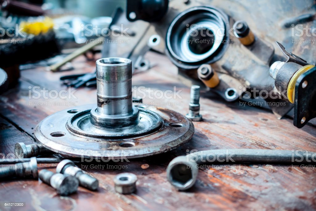 Old, oiled wheel hub lies on a wooden table stock photo