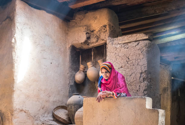 old omani lady resting in an old traditional kitchen stock photo
