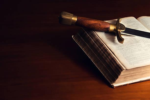 stary otwartej biblii z miecz - sword zdjęcia i obrazy z banku zdjęć