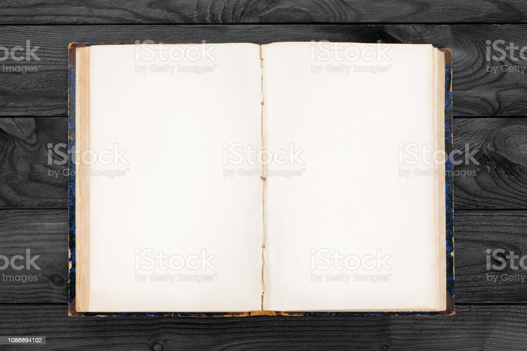 Old open book with blank pages on wooden table stock photo