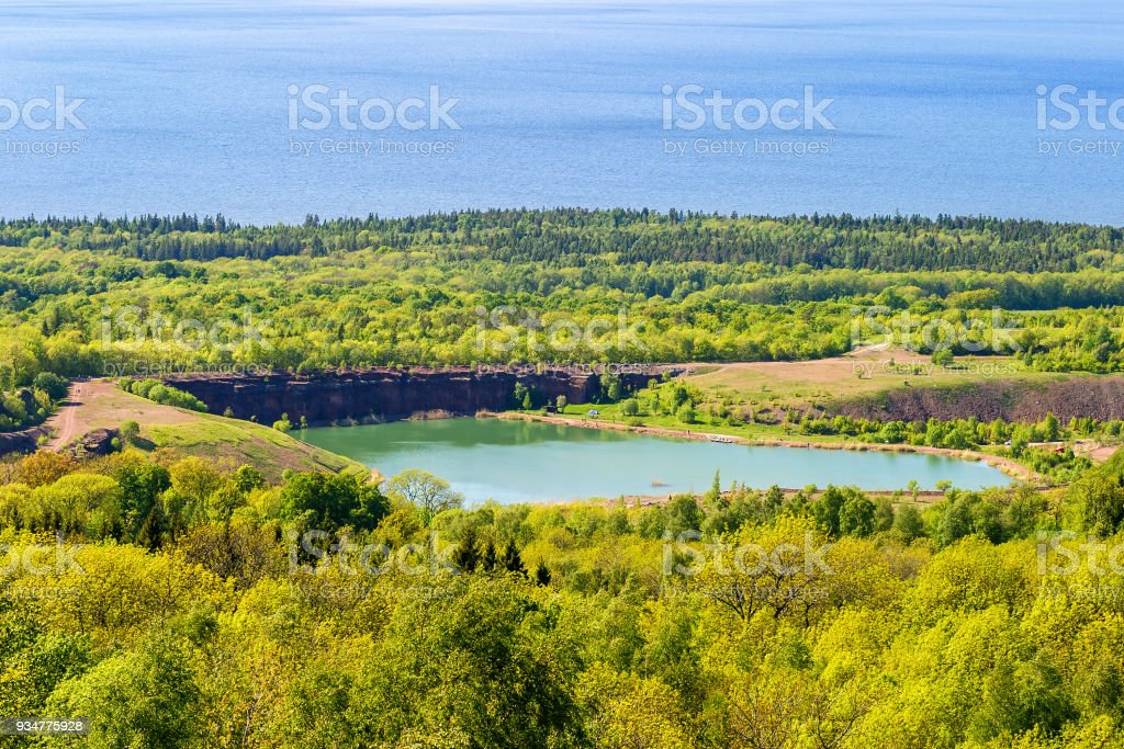 Old open pit with a lake and forest stock photo