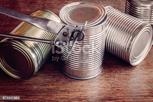 istock Old opener open to metallic can on the table in the kitchen. Canned food. Condensed milk. Healthy eating and lifestyle. 674441564
